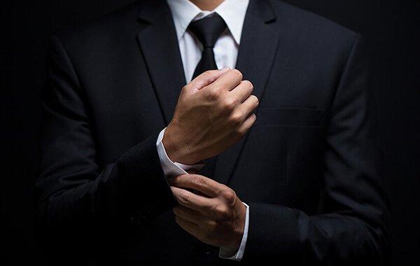 Man in suit adjusting his sleeves