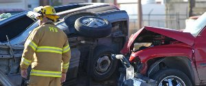 Firefighter standing near a car accident with a car turned over on its side