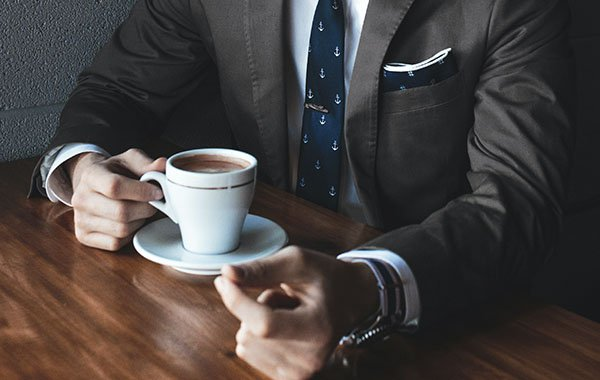 Man in suit drinking coffee