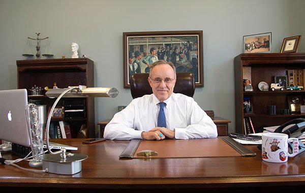 Attorney Wayne C. Arnett in White Shirt Sitting in Office