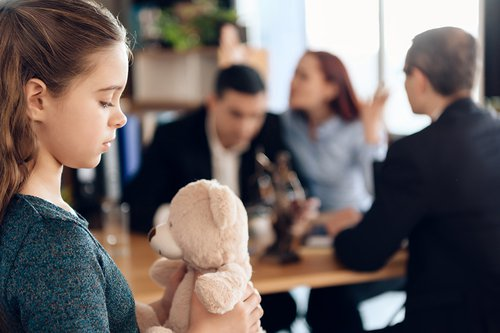 young girl holding a teddy bear with parents fighting in the background