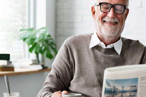 Older man with glasses reading the newspaper holding a coffee mug
