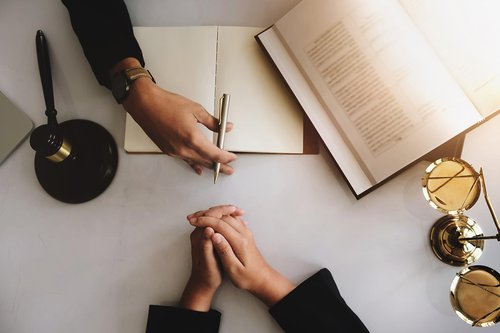 A person's hand holding a pen next to book across from another person's folded hands