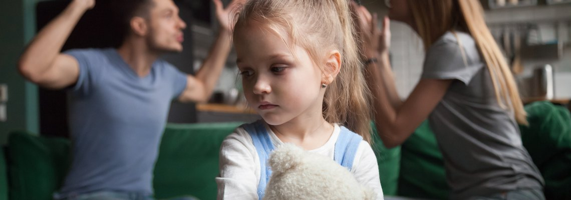 A little girl looking upset while two adults argue in the background