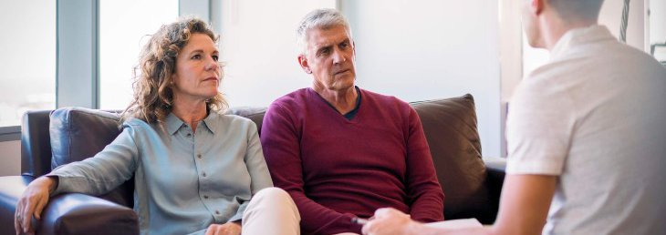 Older couple on couch speaking to younger man across from them