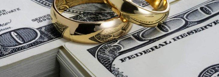 Wedding rings on stacks of one hundred dollar bills