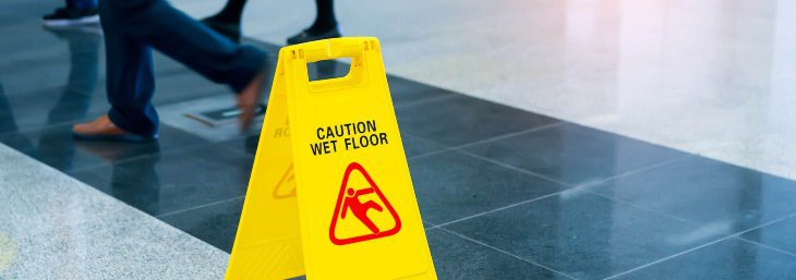 People Walking around a wet floor sign
