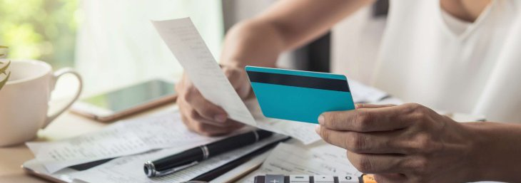 Woman making calculations holding a receipt and a credit card