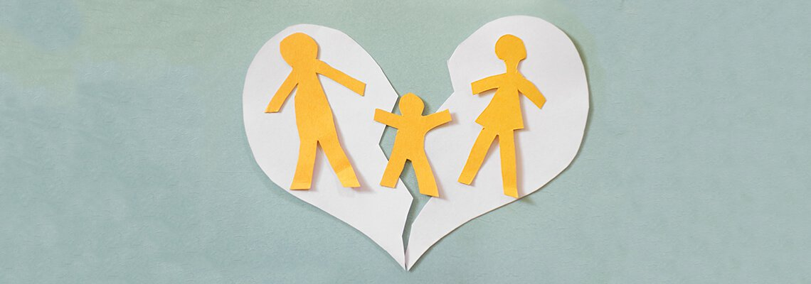 Paper heart broken with 3 human cutouts to symbolize a split family