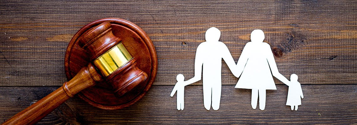 Gavel next to a paper cut out family