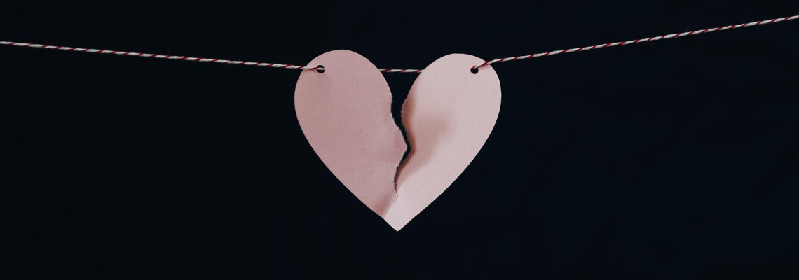 A Pink Paper Heart on a String Being Torn in Half.jpg