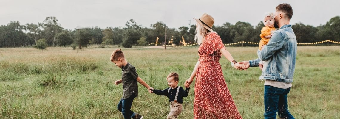 Family of five holding hands in a field