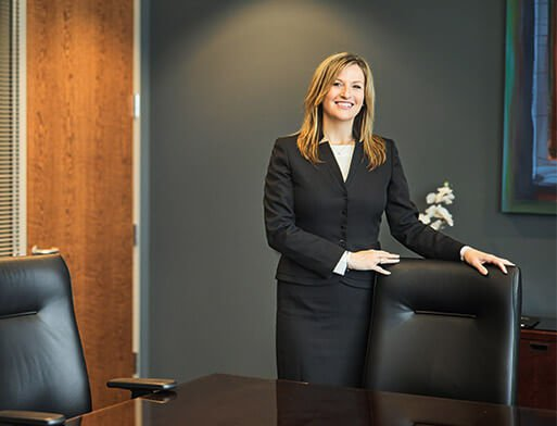 Attorney Alesia R. Strand Standing Next to a Black Chair
