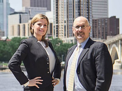 Attorney Strand and Attorney Beedem in front of a river