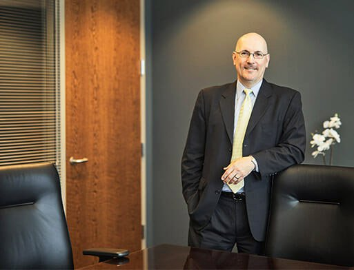 Attorney Thomas J. Beedem Standing next to a Chair