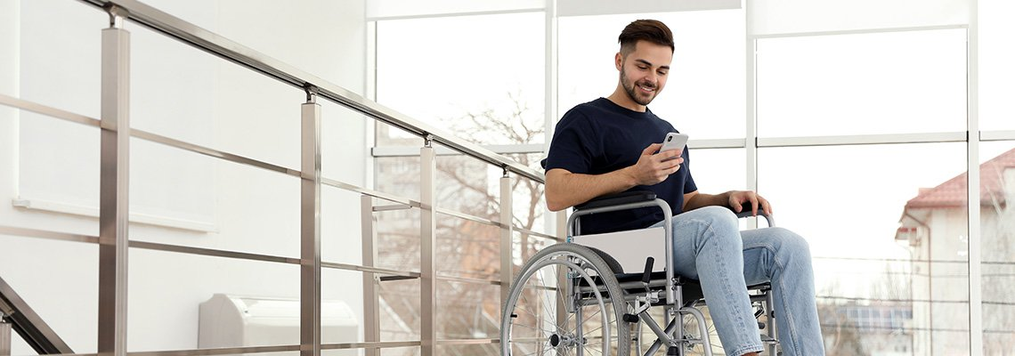 A man in a wheelchair uses his cell phone