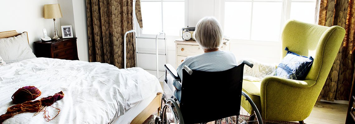 An elderly woman in a wheelchair sits alone in a room