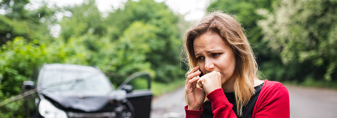 A woman talks on the phone after a serious car accident