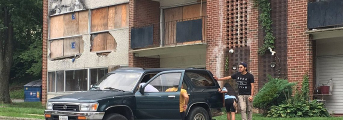 Family of four standing around an SUV outside of a condo