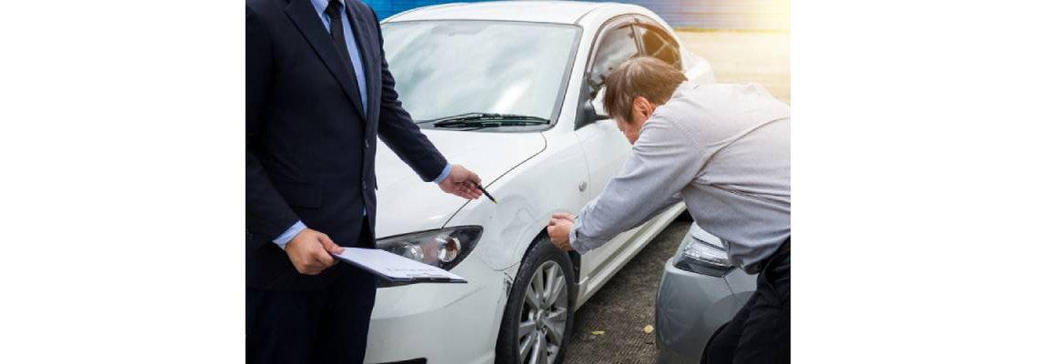 Man with an insurance adjuster examining car damage