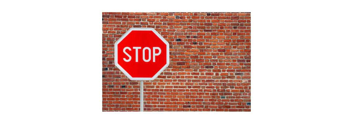 Stop sign in front of a brick wall