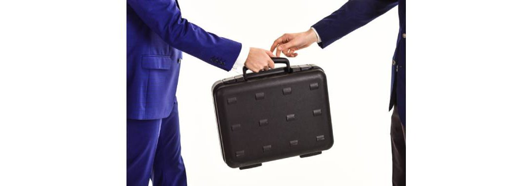 Two Businessmen handing off a briefcase