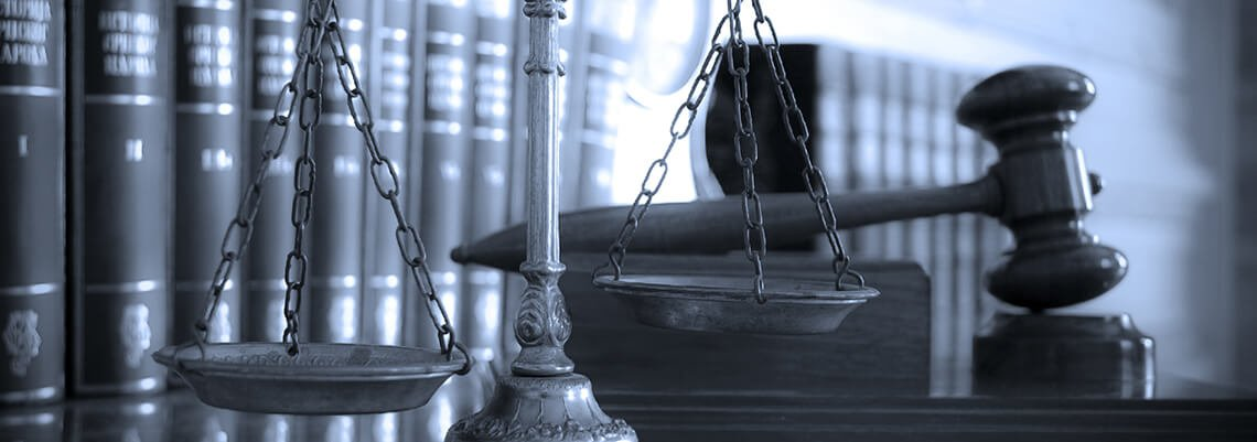 Grey-toned photo of gavel and scales of justice