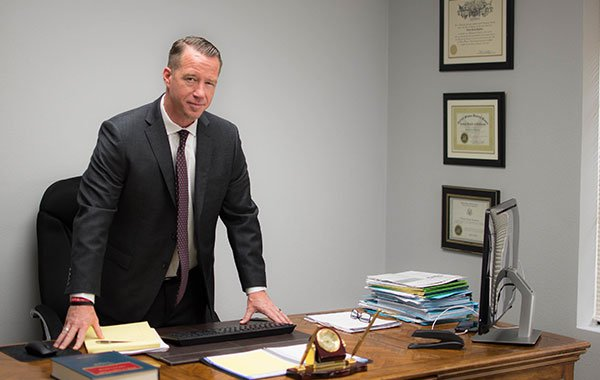 Attorney Charles Boylston Standing at Office Desk