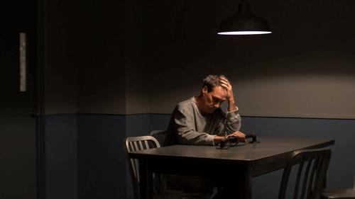 man handcuffed in interrogation room