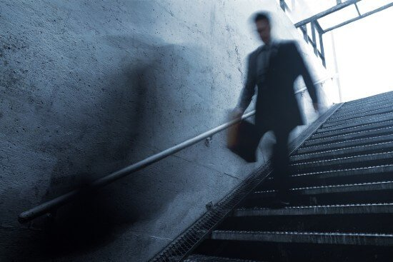 blurred person in suit walking down stairs