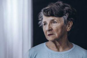 elderly woman looking out a window