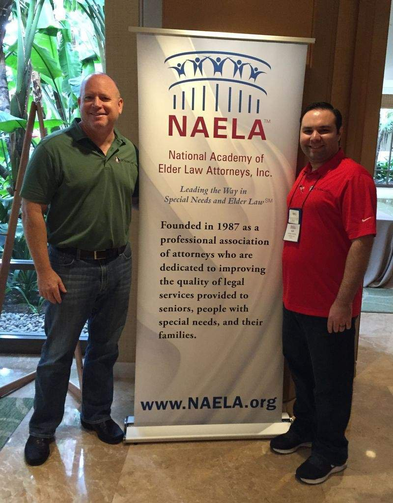 Marty Burbank and Joshua Ramirez standing next to each other by the NAELA banner