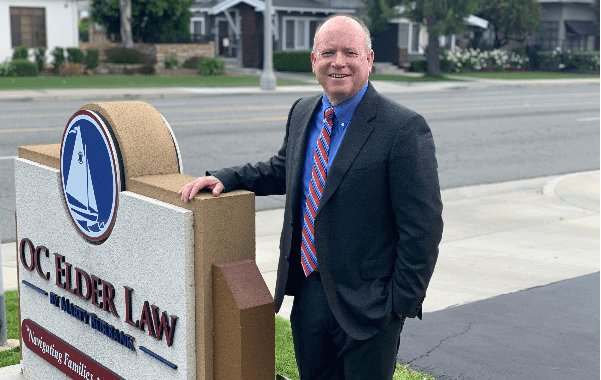 Attorney Marty Burbank Dark Blue Suit Blue Shirt Red and Blue Tie in Front of Oc Elder Law Sign