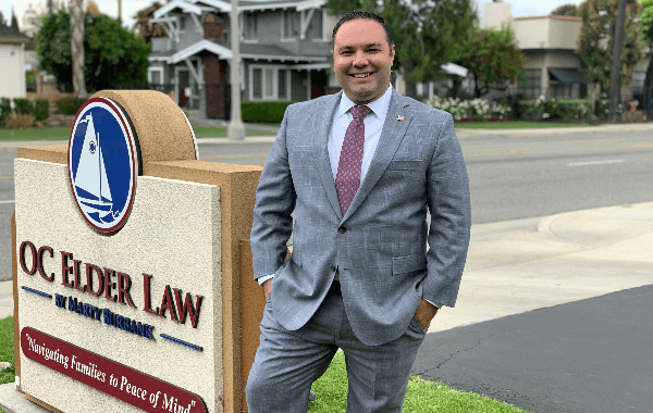 Attorney Joshua Grey Suit White Shirt Red Tie in Front of Oc Elder Law Sign