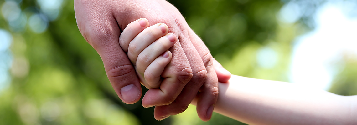 A child and adults hands holding