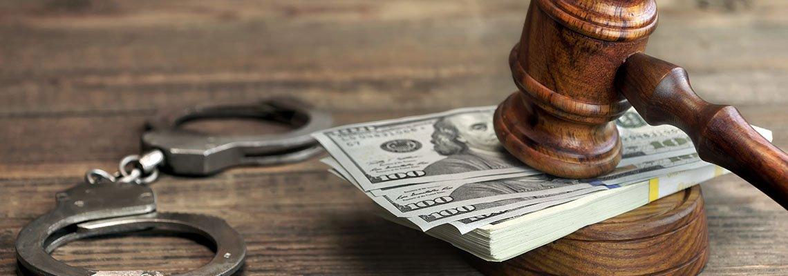 Cash for a bail bond under a gavel next to handcuffs