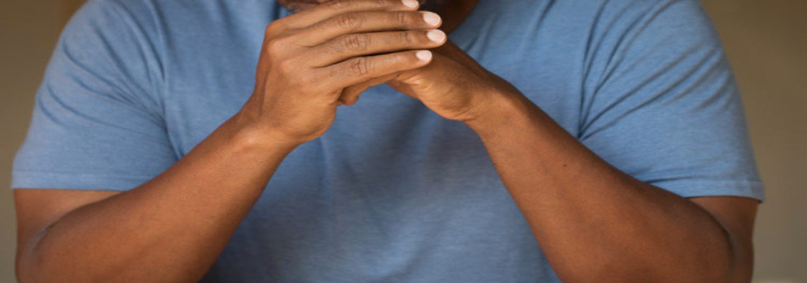 man listening with clasped hands