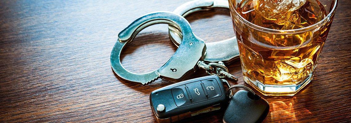 stiff drink alongside car keys and handcuffs