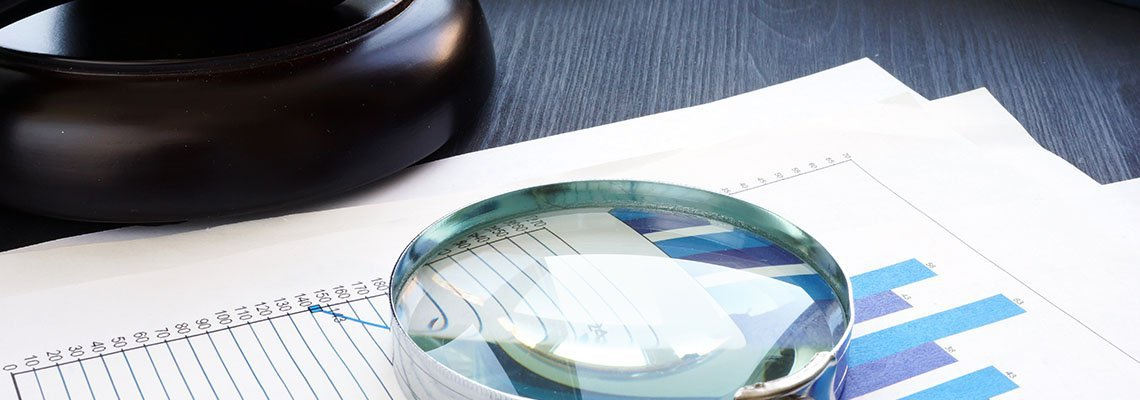Magnifying glass on stack of documents