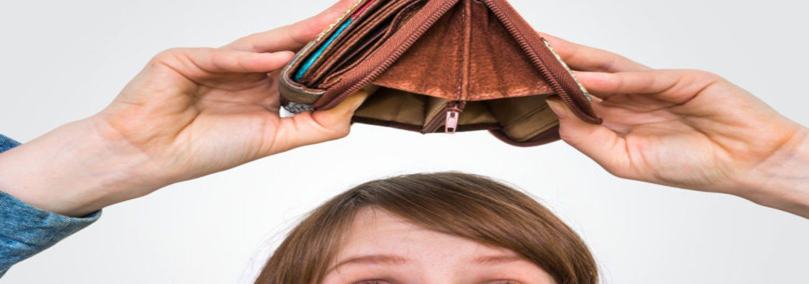 empty wallet being turned upside down by sad woman