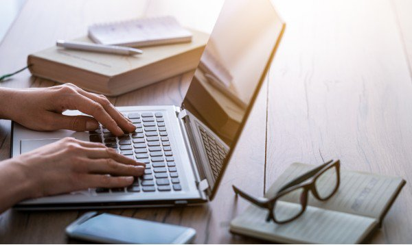 Person working at computer next to journal and glasses