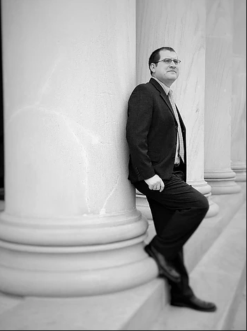 Attorney David Coates Leaning Against the Pillar