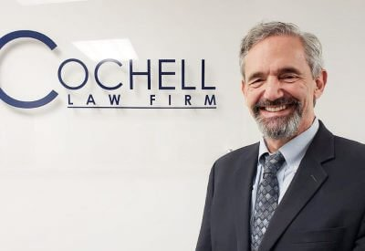 Attorney Stephen Cochell in front of Cochell Law Firm Sign