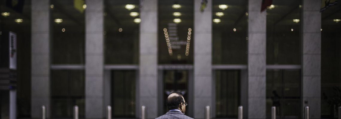 Man looking at the front doors of an office building