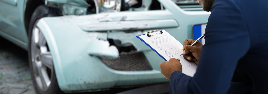 Insurance Adjuster assessing the damage to a car