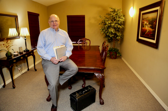Attorney Mark A. Cornelius Sitting on a Table and Holding Documents