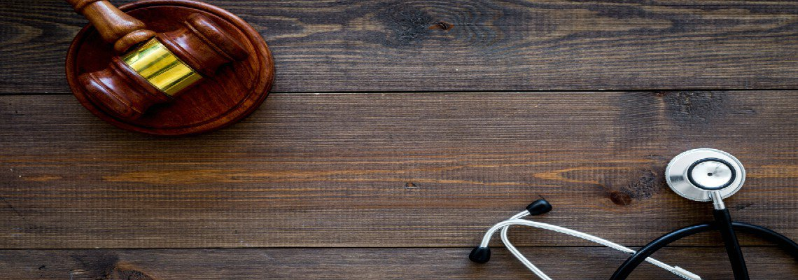 Stethoscope and a gavel on a wooden desk