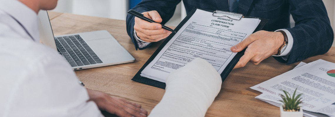 Man in suit helping man with cast fill out worker's comp form