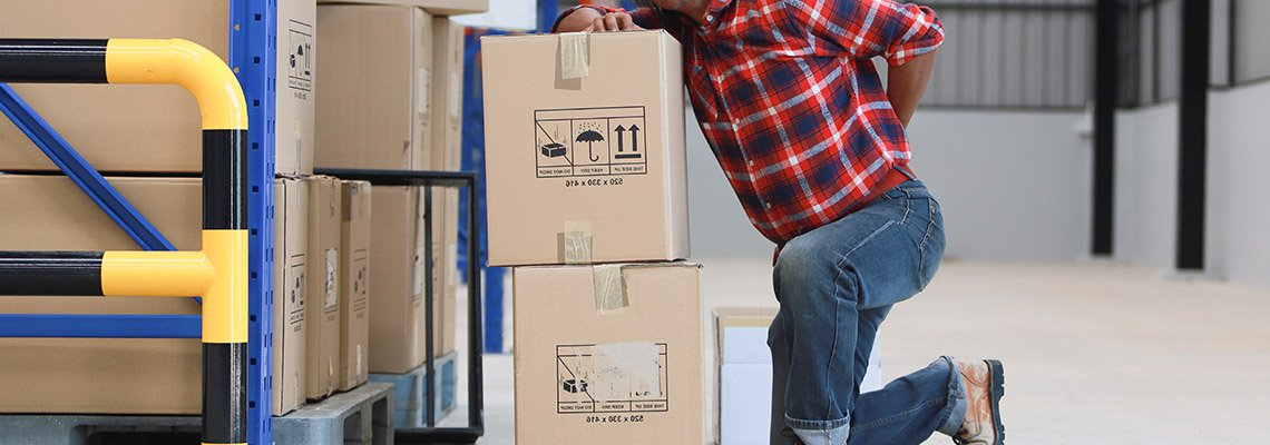 A worker holds his back in pain near heavy boxes