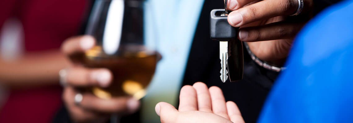 Keys in focus with person holding a glass of alcohol in the background